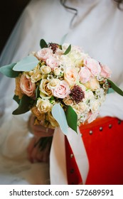 Bride in white dress sitting in chair and holding wedding bouquet in arms