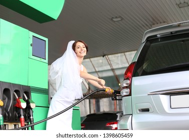 bride in a white dress and veil refuels the car at the gas station and smail