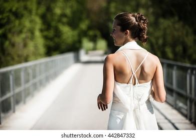 Bride in  white dress walking over a bridge