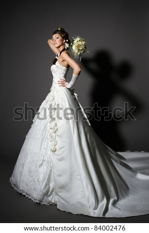 Bride in white elegance wedding dress with tail. Hand raised up with bouquet. Full length.