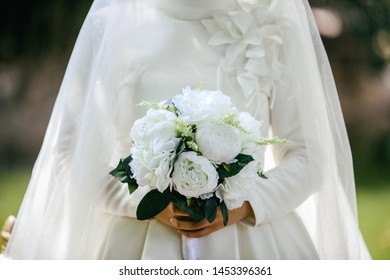 Bride in an white gown with bouquet in hands