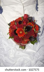 bride in white matching jacket and deep red bouquet