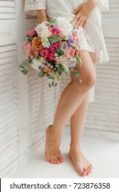 The bride in a white negligee holds a gentle pink bouquet. Morning of the bride. Beautiful female feet.