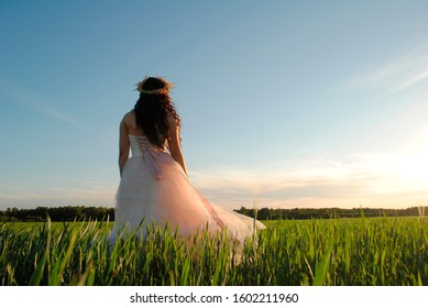 A bride in a white and pink wedding dress admires nature in a wheat field. The bride at the photo shoot posing for the camera. The sun's rays illuminate the bride.