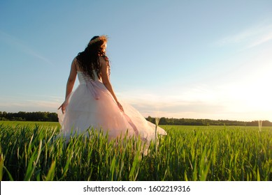 A bride in a white and pink wedding dress poses for the camera in a wheat field. The bride at the photo shoot. The bride turned her head to the side. The sun's rays illuminate the bride.