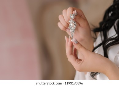 bride in a white robe, in her wedding morning, holding jewelry earrings