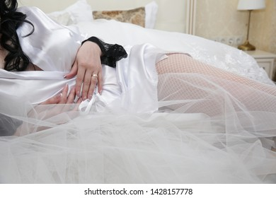 bride in white stockings and white silk peignoir in bed with silk and veil elements. Morning of the bride..