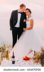Bride in white veil and groom wearing black suit embracing near the romantic dinner table on the beach at sunset