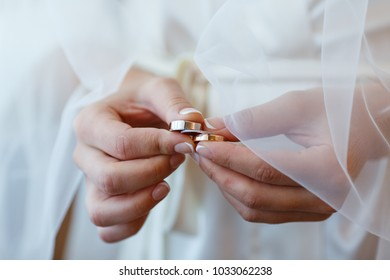The bride in a white veil holds in her hands three golden wedding rings. Bridal accessories and jewelry close-up