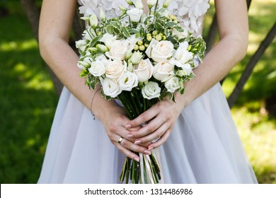 Bride in white wedding dress with a beautiful bouquet of roses