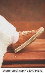 Bride in white wedding dress and brown sneakers or sports shoes. Women's foot in a sneaker, on a wooden painted bench, close-up, blurred background. Runaway bride, copy space for text.