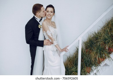 bride in a white wedding dress and groom standing at white wall