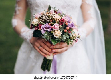 The bride in a white wedding dress holds a wedding bouquet. The bouquet consists of white, pink, purple roses, eucalyptus leaves, and pink berries. On the bride's hand is a wedding ring.
