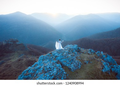 Bride in white wedding dress standing on a cliff. Aerial drone shot