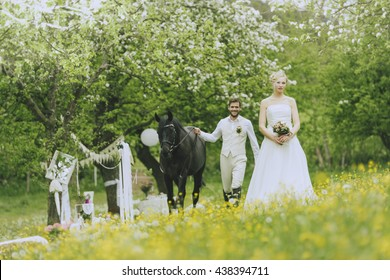 The bride in white wedding dress standing outdoors in a flowering meadow landschauft on before flowering fruit trees and holding her bridal bouquet in hand.