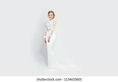 Bride woman in long white wedding dress on a white background. Luxurious dress in a woman body. Girl is preparing to marry. Perfect figure and dress women. Place for inscription on a white background