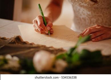 bride writing vows for wedding close up