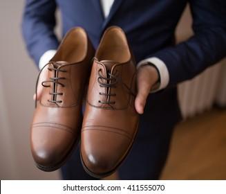 Bridegroom holding elegant brown shoes. Unrecognizable