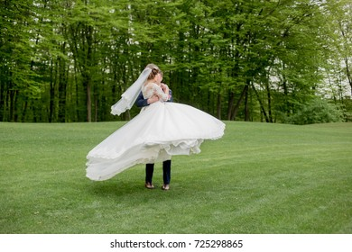 the bridegroom holds the bride in her arms in the park