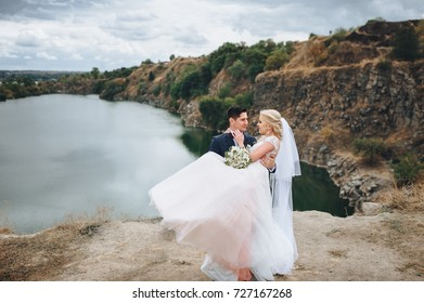 The bridegroom holds a bride in his arms in the background of a beautiful landscape on the river bank.