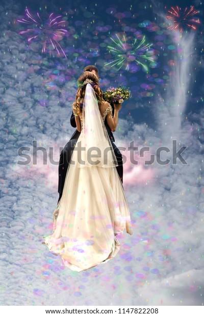 Bridegroom kisses the bride sitting on a cloud in the sky. Bride in Wedding Dress, Back of Bride. Romantic Travel Concept, Honeymoon Trip.