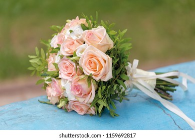 Bridegroom taking wedding beige pink lilac violet flowers in hand sunny day. Square Pink Flower box with Fresh Rose. Bouquet on the floor
