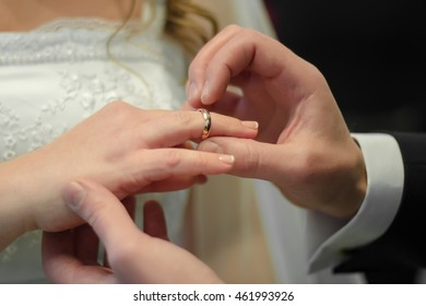 Bridegroom is wearing the ring to the bride's finger Bridegroom wears the ring to bride's finger