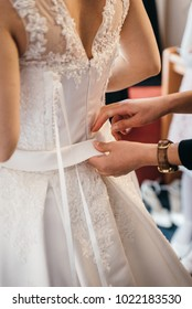 Bridemaid help to fit the wedding dress with a white ribbon