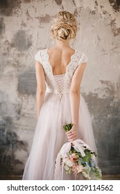 bride's back in lace dress with a bouquet