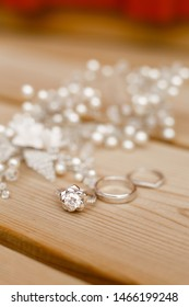 Bride's bijouterie and jewelry for hair style on wooden background. Earrings, bijouterie on a glass surface. Silver and pearls beads and wedding rings
