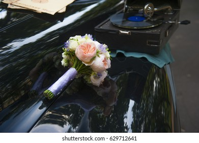 the bride's bouquet on the hood of a vintage car and a gramophone
