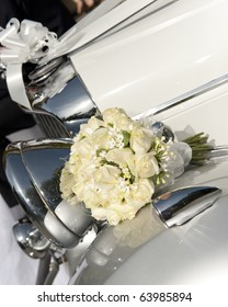 Bride's bouquet resting on a vintage wedding car