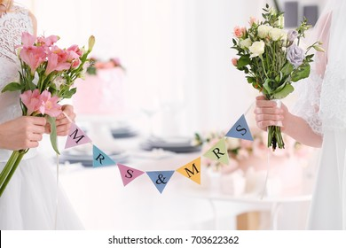 Brides with bouquets of beautiful flowers and garland on lesbian wedding