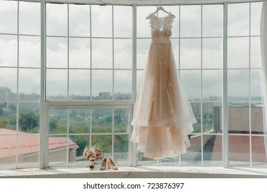 The bride's dress hangs on the window. A gentle bouquet of the bride and women's shoes stand on the windowsill