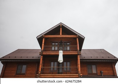 The bride's dress weighs on the balcony of the house