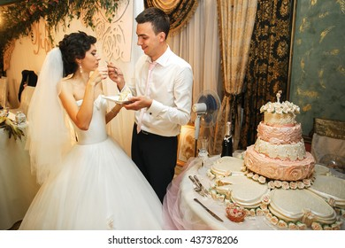 The brides eatting a wedding cake