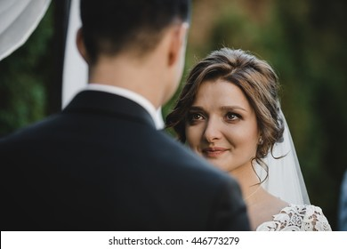 Bride's eyes sparkle while she looks at a groom standing under the wedding altar