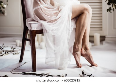 bride's feet. beautiful girl in white transparent boudoir gown of tulle and lace sitting on a chair