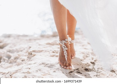 Brides feet with beautiful jewelry stepping forward. Brides legs close up.