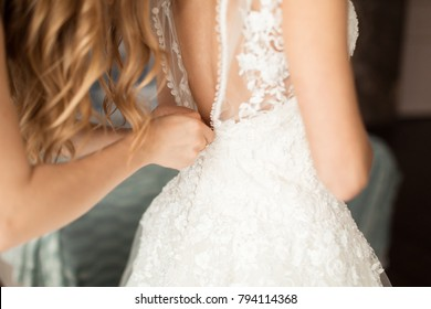A bride's friend helps to tie a dress. The bride's fees