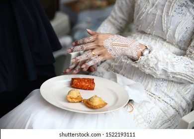 Bride's getting ready with white henna on hands going to eat some food