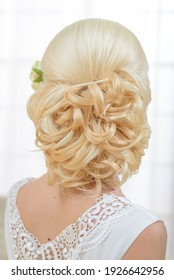 Bride's hairstyle close up. A girl in a white dress preparing for a wedding ceremony. Jewelry and flowers in the hair of the bride.