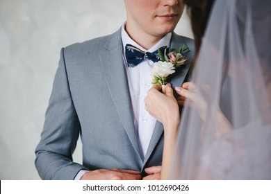The bride's hand puts on a boutonniere flower on the groom's jacket. Bride puts a buttonhole on a grooms suit