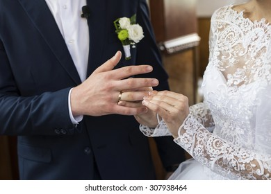 bride's hand putting a wedding ring on the groom's finger