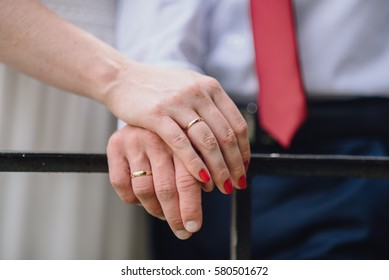 bride's hand with red manicure and groom in a red tie
