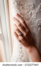 Bride's hand with a ring on her finger. Touching the wedding dress