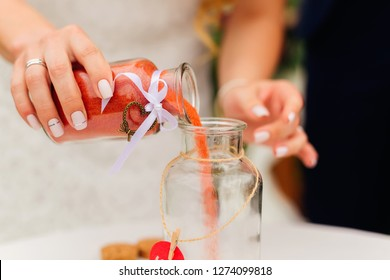 bride's hand with a wedding ring that holds a jar of red sand and pours it into a unity vase. wedding sand ceremony