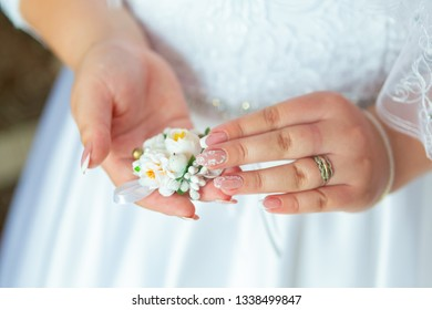 Bride's hands with a bouquet for the groom. place for text