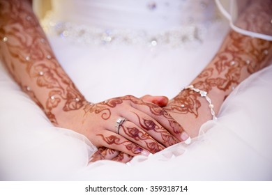 brides hands in henna with ring