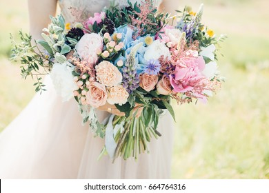 bride's hands hold a beautiful bridal bouquet of peony. fine art photography.